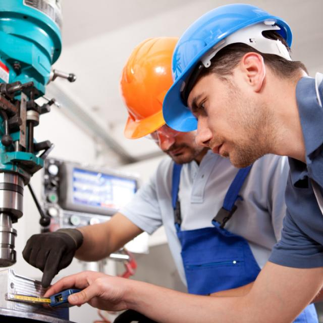 two engineers working together at a machine