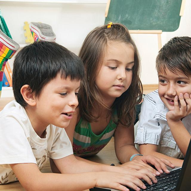 three young students working on a laptop together