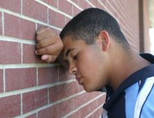 young man rests his head against his arm in front of a brick wall