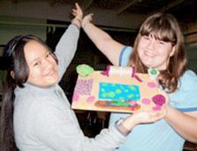 two teenage girl students high-fiving each other, showing a project