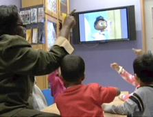 Teacher watches educational video program with young students