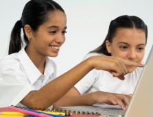 two teen student girls working together at a computer