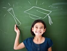 girl standing at blackboard with diploma and graduation cap drawn on it