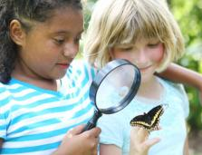 two elementary school age girls looking at a butterfly through a magnifying glas