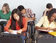 high school students writing at desks in a classroom