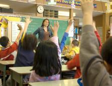 teacher in front of students raising their hands