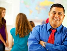 Young male teacher smiling at camera with students behind him