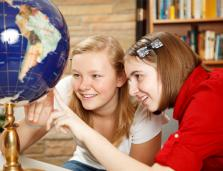 two girls looking at a world globe and smiling