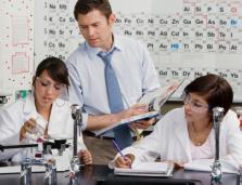 science teacher watching two students working at laboratory activity