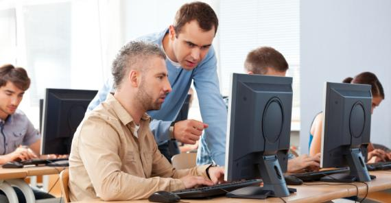 adult students in computer classroom with teacher