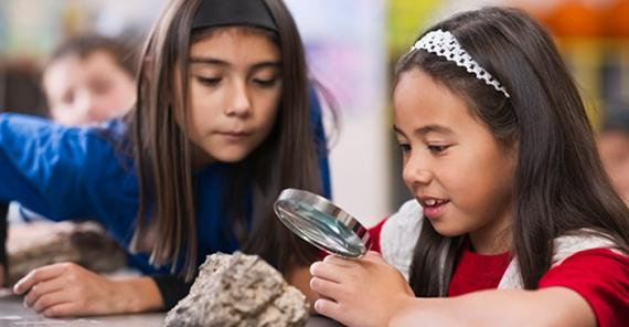 two girls examining a rock with a magnifying glass in classroom