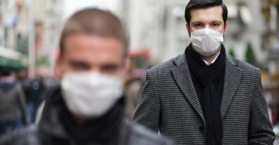 two men walking down a city street, wearing protective masks