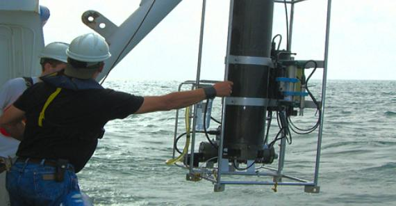 men lowering MIMS system into the water