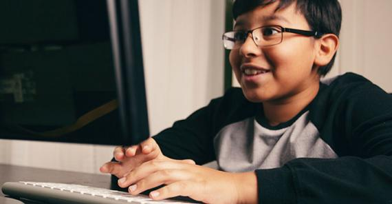 smiling boy working on a computer