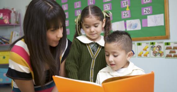 teacher reads with two young students