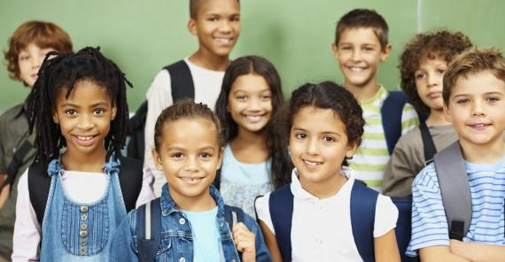 young school-age children smiling at the camera