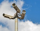 three outdoor security cameras on a pole